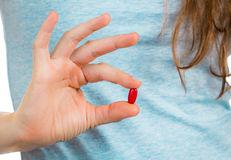 δάχτυ-α-που-κρατούν-ένα-κόκκινο-χάπι-39083916